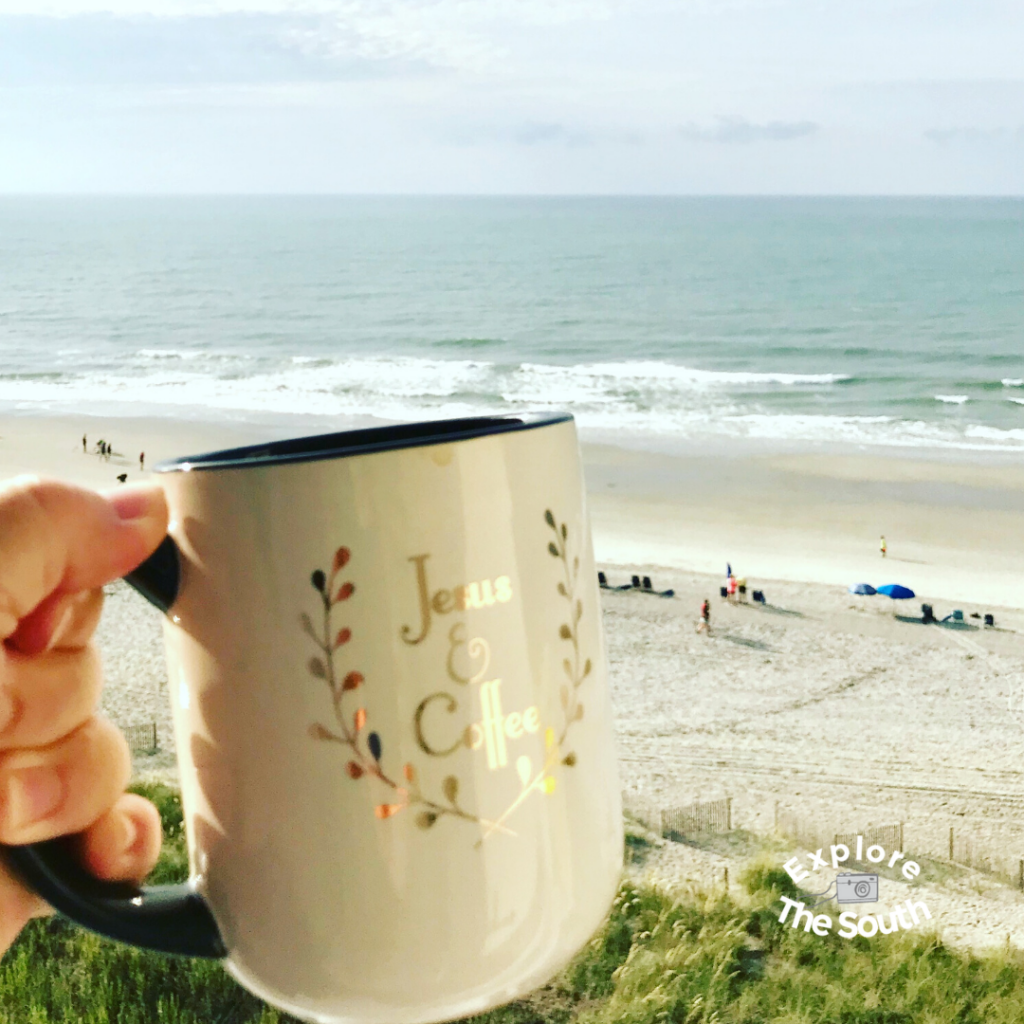 A coffee mug that says Jesus and Coffee being held up with a view of the ocean in the background