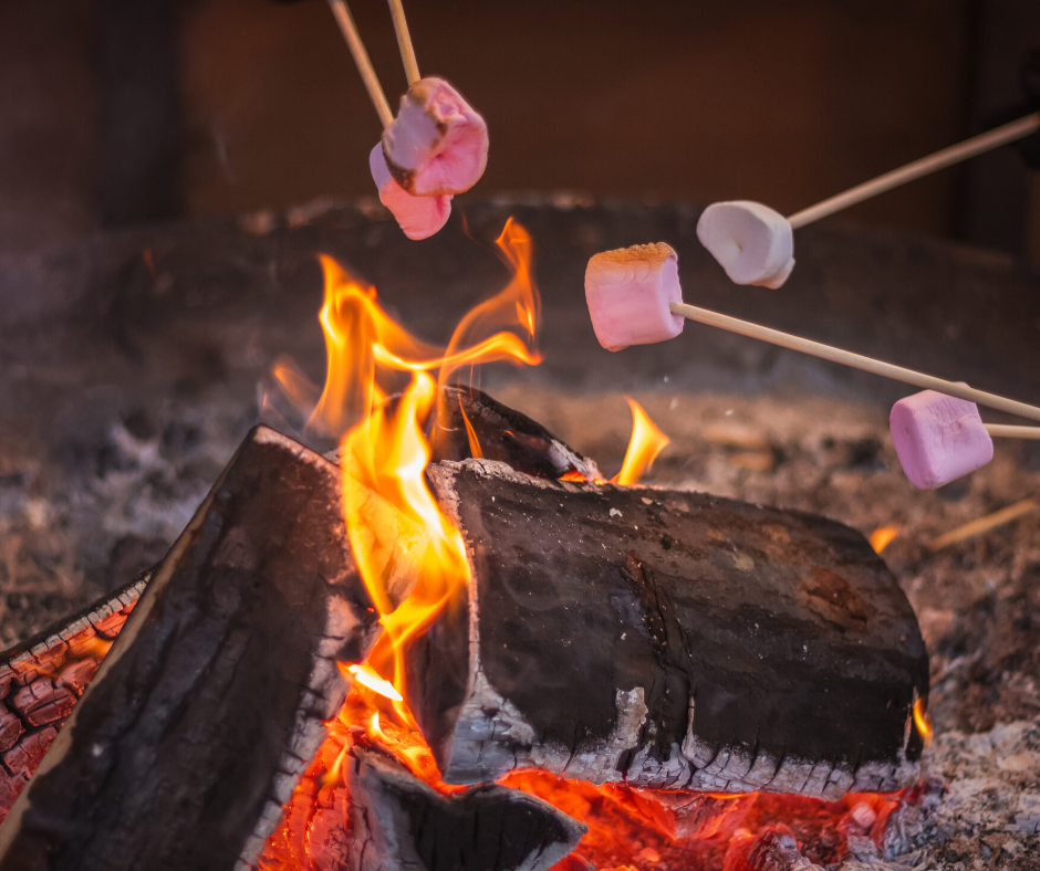 A roaring campfire with marshmallows being roasted over the open flames
