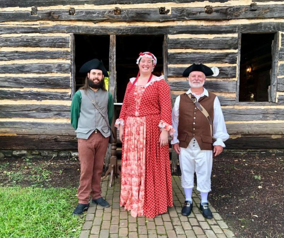People dressed in Pioneer costumes standing in front of a log cabin